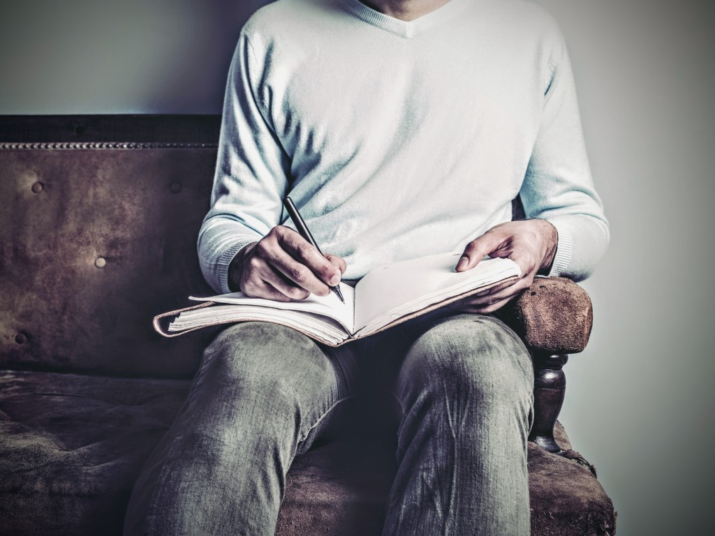 A young man is sitting on an old sofa and is writing in a notebook